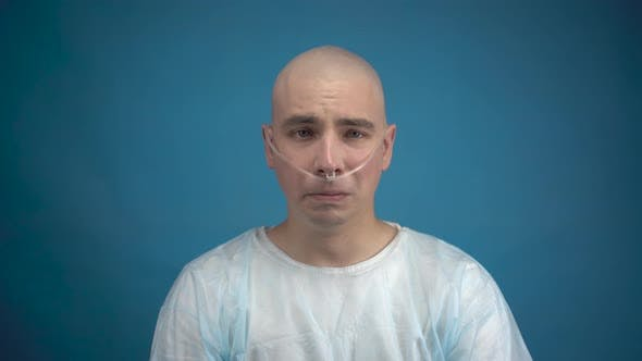 Thumbnail for A Bald Young Man with Oncology Looks at the Camera and Cries on a Blue Background. The Patient