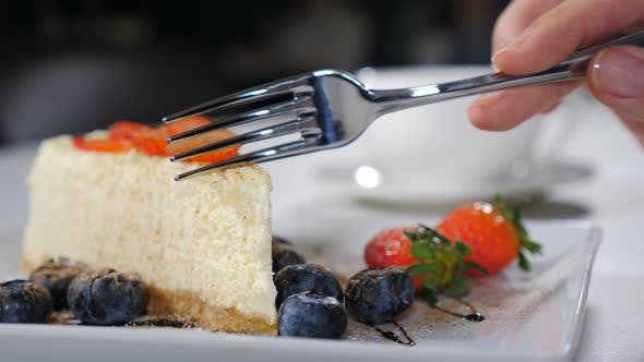 Eating Delicious Cheesecake. Taking Bite of Caramel Cheesecake with Fork. Baking and Confectionery