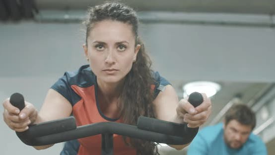 Thumbnail for Middle Shot of Focused Concentrated Sportswoman Cycling in Sports Club on Exercise Bike. Young Slim