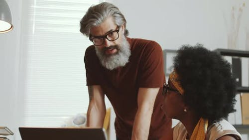 Bearded Businessman Discussing Work with Afro-American Female Colleague
