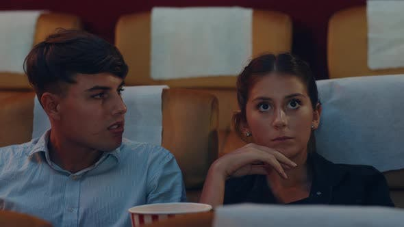 young caucasian couple using smartphone while watching film in movie theater.