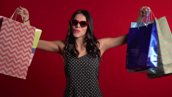 Thumbnail for Happy Young Woman with Colorful Paper Bags After Shopping Isolated on Red