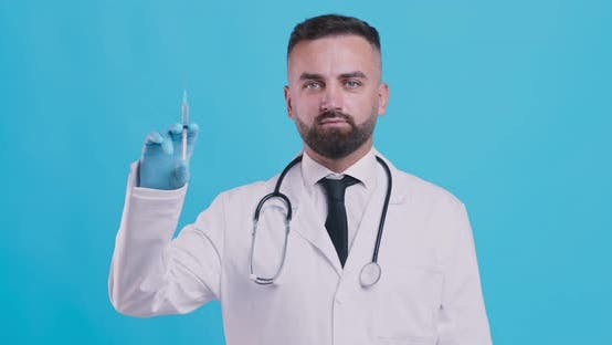 Thumbnail for Vaccination Campaign. Serious Doctor Showing Syringe with Vaccine for Injection
