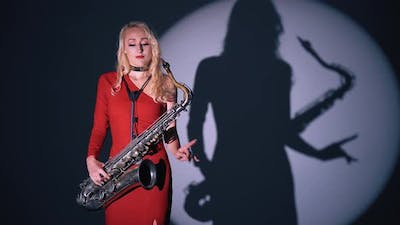 Girl with Saxophone Dancing. Jazz Melody