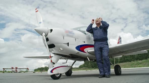 Cover Image for Mature Pilot in Sunglasses Standing before Plane