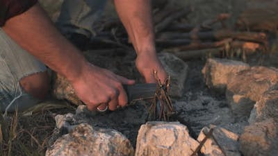 Man Hands Lighting a Fire Starting Campfire with Fire Starting Tools and Knife Making a Camp to Stay