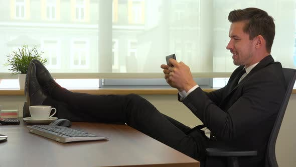 Thumbnail for An office worker sits in front of a computer with legs on the desk and plays a game on smartphone