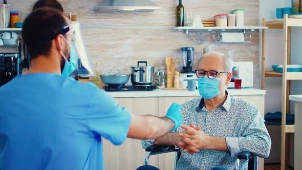 Social Worker Offering Pills to Disabled Senior Man