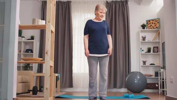 Thumbnail for Seniorin entspannt im hellen Wohnzimmer