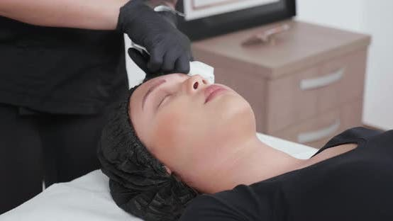Woman Cosmetologist Using a Clean Cloth To Remove Paint Residues From the Eyebrows