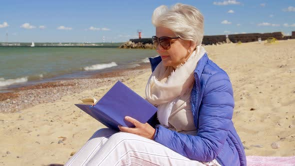 Thumbnail for Happy Senior Woman Reading Book on Summer Beach