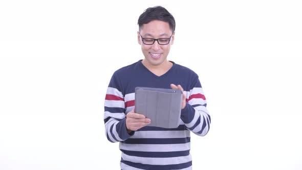 Thumbnail for Happy Japanese Hipster Man Talking While Using Digital Tablet