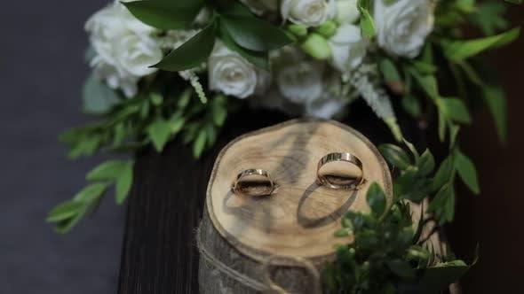 Thumbnail for Schöne Eheringe liegen auf Holzständer mit Hochzeit Braut Blumenstrauß
