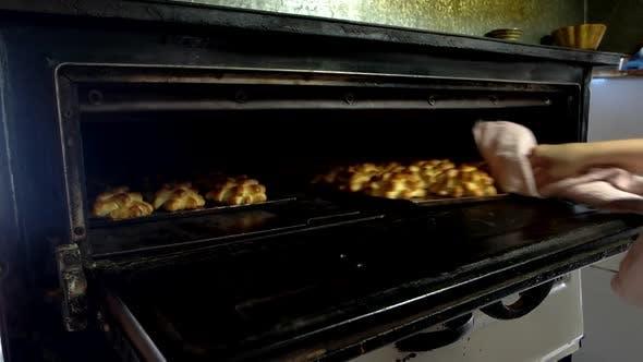 Bäcker entfernen Tablett mit gebackenem Gebäck aus dem Ofen