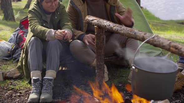 Thumbnail for Senior Couple Sitting by Campfire and Talking
