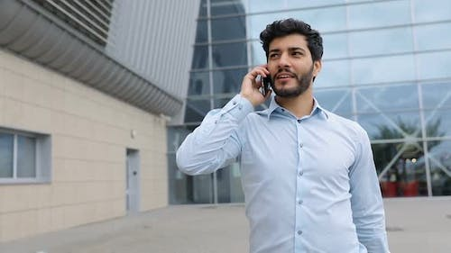 Handsome Man Talking On Phone Near Office Outdoors