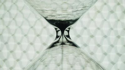 Transparent hourglass and bokeh lights.