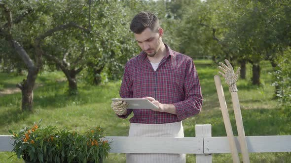 Thumbnail for Young Farmer in Garden Gloves Using the Tablet Standing Behind the Fence in the Foreground