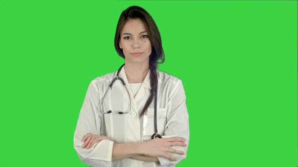 Beautiful Female Doctor Standing with Her Arms Crossed and Nodding Her Head on a Green Screen