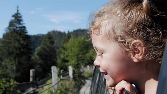 Thumbnail for Happy Cute Little Girl with a Smile Stuck Out of the Car Window Into the Wind. Slow Motion