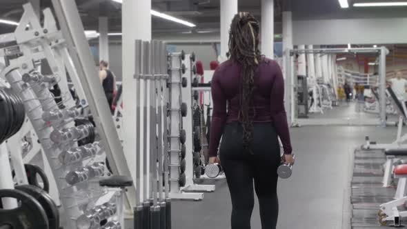 Sports Training  Black Woman Walks Forwards in the Gym Holding Dumbbells