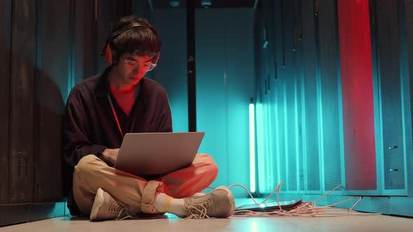 Asian IT Specialist Coding on Laptop in Data Center