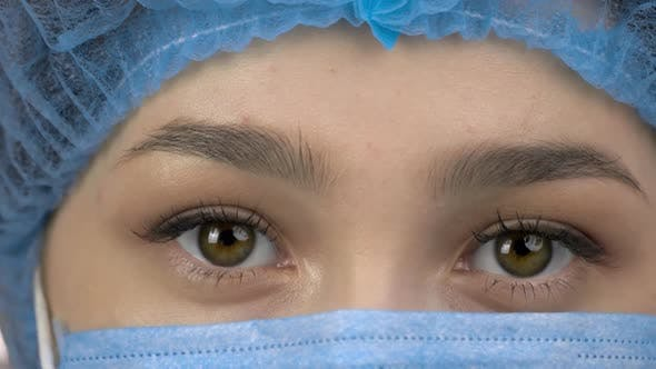 Closeup Eyes of Young Female Surgeon Doctor or Intern Wearing Protective Mask and Hat