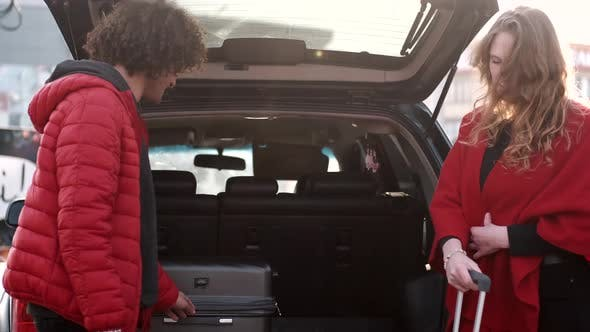 Happy Couple Taking Out Luggage From Car Trunk