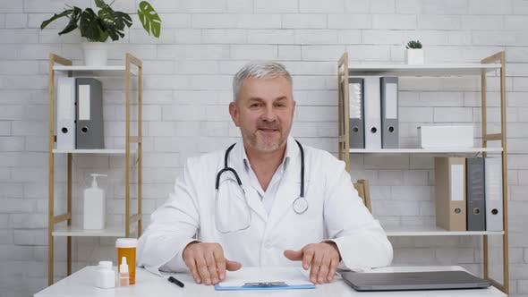 Male Doctor Consulting Talking To Camera Sitting In Clinic Office