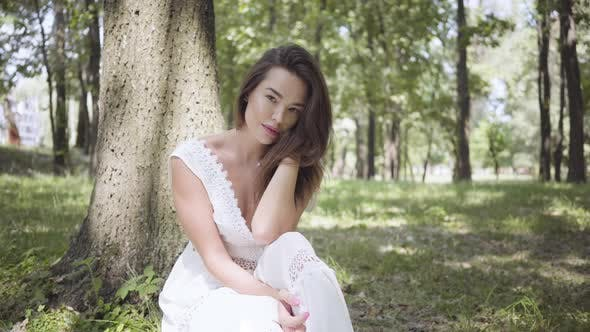 Cover Image for Portrait of Cute Young Girl with Long Brunette Hair Wearing a Long White Summer Fashion Dress
