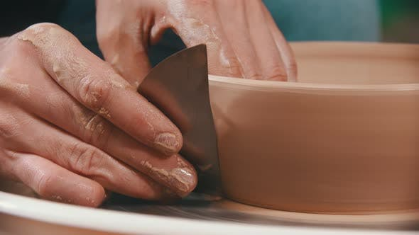 Thumbnail for Pottery - the Master Is Helping with a Special Metal Spatula To Smooth the Surface of the Clay Bowl