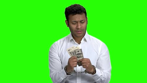 Confused Handcuffed Businessman Holding Money