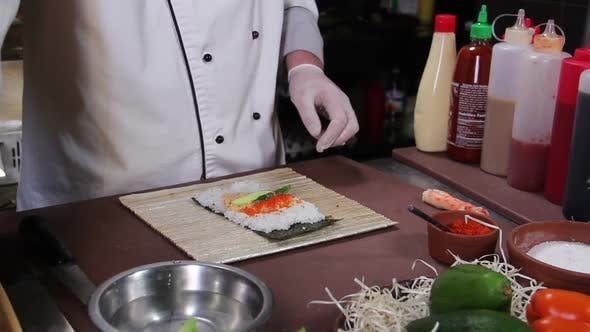 Thumbnail for Chef Making Delicious Sushi Rolls With Cucumber and Red Caviar