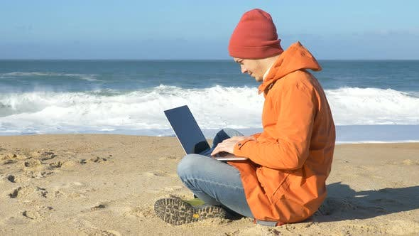 Man Enjoys Distance Work Sitting on Beach Sand with Laptop