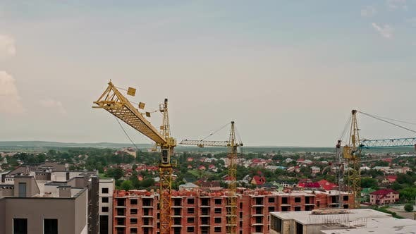 Thumbnail for Aerial Drone View. High Cranes Works on Building Site with a House. Flying Around
