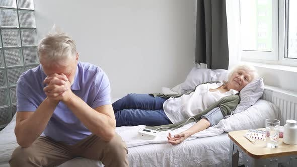 Mature Woman Is Lying on the Bed and Is Sick and Her Husband Is Sitting Next To Her and Is Very