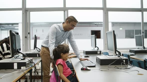 Tutor Standing Next to Girl Helping with Working on Computer