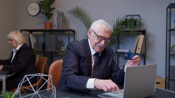 Senior Businessman Grandfather Director Shopping Online and Paying with Credit Card in Modern Office