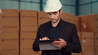 Factory Manager Using Tablet Computer in Warehouse or Factory