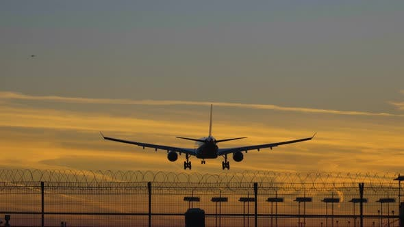 Thumbnail for Silhouette of Airplane Landing at the Airport at Colorful Sunset