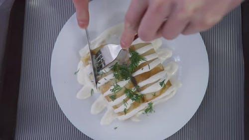 Top View Male Hands Cutting Stuffed Rolled Pancakes with Topping on Dinner Plate