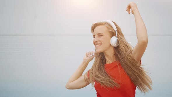 A Young Girl in Headphones is Listening to Music and Amusingly Dancing on a Light Background