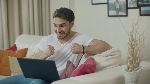 Thumbnail for Happy Man Celebrating Success with Laptop Computer on Sofa at Home