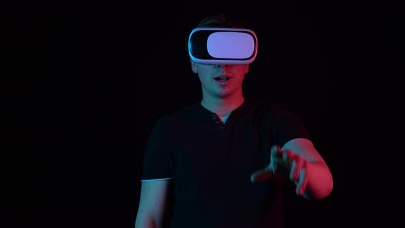Thumbnail for Young Man in VR Glasses. A Man Immersed in Virtual Reality Makes Movements with His Hands. Blue and