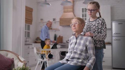 Fürsorgliche Enkelin machen Massage zu Großmutter