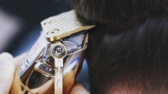Hairdresser Does Haircut to Young Client with Golden Machine