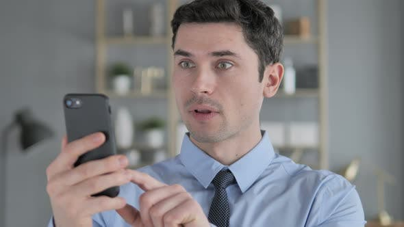 Thumbnail for Young Man in Shock While Using Smartphone, Wondering
