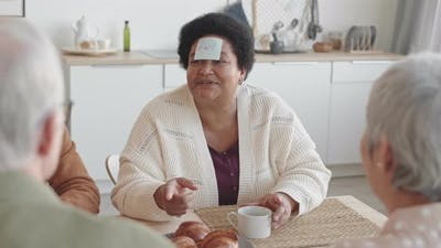 Woman with Sticky Note Saying Owl on Forehead