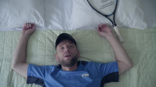 Thumbnail for Handsome Tired Tennis Player in Sports Equipment Is Lying on the Bed with a Tennis Racket