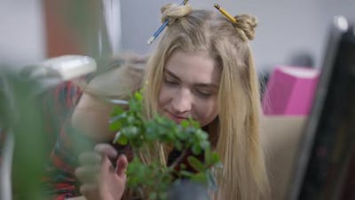 Charming Hipster Millennial Woman Looking at Plant in Pot Smiling